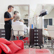 Hairstylist Straightening Client's Hair At Salon - Stock Photo