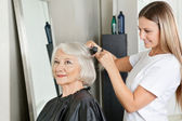 Hairstylist Straightening Woman's Hair At Salon — Stock Photo