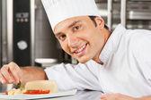Happy Male Chef Garnishing Dish — Stock Photo