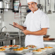 Male Chef With Clipboard At Kitchen - Stock Photo