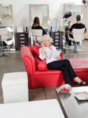 Client Holding Magazine While On Call At Salon — Stock Photo