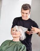 Hairstylist Straightening Senior Woman's Hair — Stock Photo