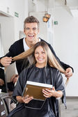 Hairstylist With Client Holding Mirror At Salon — Stock Photo