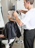 Hairdresser Straightening Female Client's Hair — Stock Photo