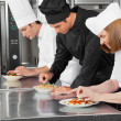 Chefs Garnishing Dishes On Counter — Stock Photo #22501225