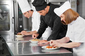 Chefs Garnishing Dishes On Counter — Stock Photo