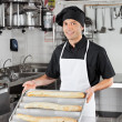 Male Chef Presenting Loafs In Kitchen — Stock Photo #23297858