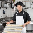 Male Chef Presenting Loafs In Kitchen - Stock Photo