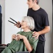 Woman With Coffee Cup And Hairdresser Holding Straightener — Stock Photo #23298380