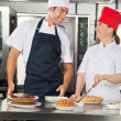 Happy Chefs Preparing Sweet Dishes in Kitchen — Stock Photo