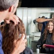 Stock Photo: Hairdresser Setting Client's Hair While Looking At Mirror