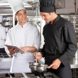Male Chef Assisting Colleague In Preparing Food — Stock Photo