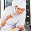 Stock Photo: Happy Chef Adding Spices To Dish