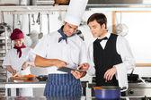 Garçom e chef usando tablet digital na cozinha — Foto Stock