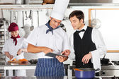 Waiter And Chef Using Digital Tablet In Kitchen — Stock Photo