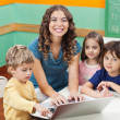 Stock Photo: Beautiful Teacher And Students With Laptop In Classroom