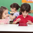 Boy Using Digital Tablet With Friend At Desk - Foto de Stock