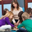 Teacher And Students Reading Book In Preschool — Stock Photo