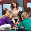 Stock Photo: Teacher And Students Reading Book In Preschool