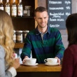 Bartender Serving Coffee To Female Friends At Cafe - Stock Photo
