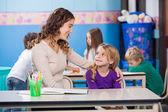 看着幼儿园老师的小女孩 — 图库照片