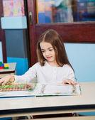 Meisje openen van pop-up boek bij bureau in — Stockfoto
