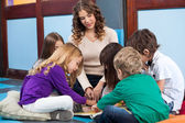 Teacher And Students Reading Book In Preschool — Stockfoto