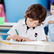 Boy Drawing With Sketch Pen At Desk In Kindergarten — Stock Photo #25932823
