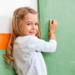 Girl Writing On Green Chalkboard In Classroom — Stock Photo