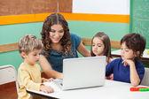 Profesor y alumnos con el portátil en clase — Foto de Stock