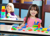 Girl With Construction Block While Friend Playing In Background — Stock Photo