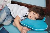 Junge liegend auf herzförmige kissen in — Stockfoto