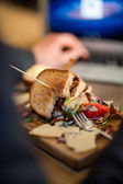 Half Eaten Sandwich On Wooden Plate — Stock Photo