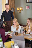Female Friends With Food On Table While Waiter Holding Menu — Stock Photo