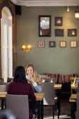 Mutlu genç bir kadın arkadaşıyla kahve içer — Stok fotoğraf
