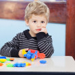 Bored Boy Holding Blocks Sitting At Desk In Classroom — Stock Photo