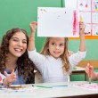 Teacher With Girl Showing Drawing At Desk — Stock Photo #26117843