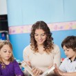 Young Teacher And Children Reading Book In Classroom — Stock Photo #26118059