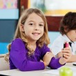 Girl Holding Color Pencils With Friend Drawing In Background — Stock Photo