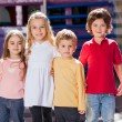 Stock Photo: Children Standing Arms Around In Kindergarten