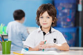 Cute Boy With Paper And Sketch Pen At Desk — Stock Photo