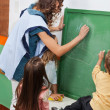 Teacher And Students Writing On Chalkboard In Classroom — Stock Photo