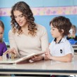 Children And Teacher Reading Book In Preschool — Stock Photo #26256143