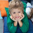 Stock Photo: Boy With Head In Hands Lying On Cushions In Kindergarten