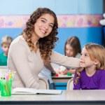 Kindergarten Teacher With Little Girl In Classroom — Stock Photo #26256567