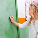 Girl Writing On Green Chalkboard In Kindergarten — Stock Photo