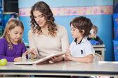 Children And Teacher Reading Book In Preschool — Stock Photo