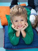 Junge mit kopf in händen liegend auf kissen im kindergarten — Stockfoto