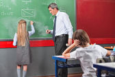 Schoolgirl Writing With Teacher Standing By Board In Classroom — Stock Photo