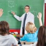 Teacher Teaching While Students Raising Hands — Stock Photo